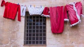 Santa Claus viste en el estante de sequía para secarse al aire libre fotos de archivo libres de regalías