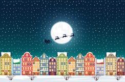 Santa Claus vuela sobre una ciudad vieja nevosa adornada de la ciudad cerca de la luna en la Nochebuena Imágenes de archivo libres de regalías