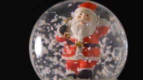 Santa Claus w śnieżnej kuli ziemskiej na czarnym tle zbiory wideo