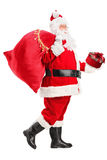 Santa Claus walking with bag and gift in his hands Royalty Free Stock Images