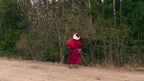 Santa Claus walking near apple tree stock video