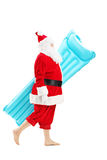 Santa claus walking with a swimming mattress. Full length portrait of a Santa claus walking with a swimming mattress isolated on white background Stock Photo