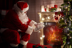 Santa Claus. Warming his hands at fire fireplace Stock Image
