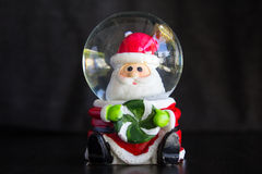 Santa Claus Water Dome Snow Glass Ball. Sitting holding candy and dark background front view Stock Images