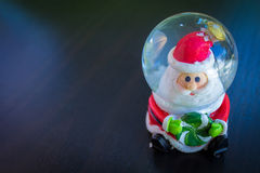 Santa Claus Water Dome Snow Glass Ball. Sitting holding candy and dark background front view Stock Image