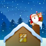 Santa Claus waving hand in the chimney House with carrying a gift bag Royalty Free Stock Photo