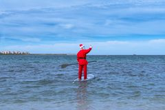 Santa Claus is waving over his surfboard. royalty free stock images