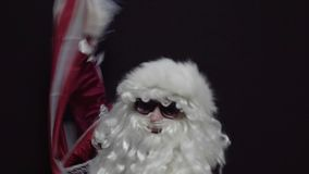 Santa claus waving a US flag against black background - the concept of Christmas or Independence Day USA.  stock footage