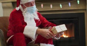 Santa Claus wearing face mask giving gift box