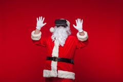 Santa Claus wearing virtual reality goggles, on a red background. Christmas.  stock photo