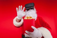 Santa Claus wearing virtual reality goggles and a red bucket with popcorn, on a red background. Christmas Royalty Free Stock Images