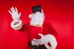 Santa Claus wearing virtual reality goggles and a red bucket with popcorn, on a red background. Christmas Royalty Free Stock Photography