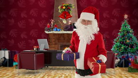 Santa Claus weighting presents in his modern Christmas Office, stock footage Royalty Free Stock Images
