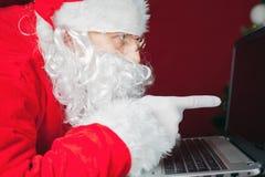 Santa Claus, welche die Laptop-Computer, zeigend auf Schirm verwendet Stockfotos