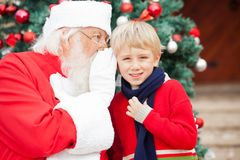 Santa Claus Whispering In Boy's Ear Royalty Free Stock Photography