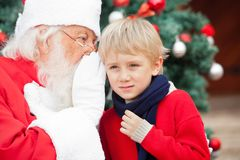 Santa Claus Whispering In Boy's Ear Stock Photos