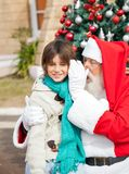 Santa Claus Whispering In Boys Ohr Stockfotografie