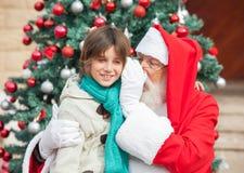 Santa Claus Whispering In Boys Ohr Lizenzfreie Stockbilder