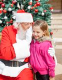 Santa Claus Whispering In Girl's Ear Against Royalty Free Stock Photo