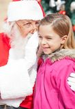 Santa Claus Whispering In Girl's Ear Stock Image