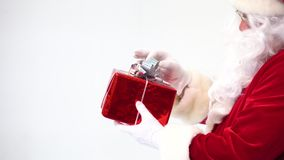 Santa Claus on a white background. A close-up of a gift box on a hand is framed.