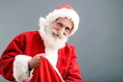 Santa Claus With A White Beard Pulls A Gift Out Of The Bag. Santa Claus with a white beard wearing Santa outfit standing on the gray background and pulls a gift stock photo