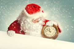 Santa Claus  with white blank banner holding a clock Royalty Free Stock Images