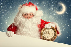Santa Claus  with white blank banner holding a clock Stock Photo