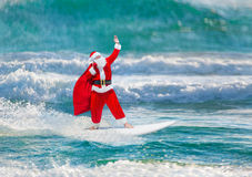 Santa Claus windsurfer with gifts sack surfing at ocean waves Stock Image