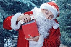 Santa Claus in a winter forest. Christmas and new year holiday. A guy dressed as Santa Claus in a winter forest opens gift box royalty free stock photography
