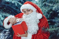Santa Claus in a winter forest. Christmas and new year holiday. A guy dressed as Santa Claus in a winter forest opens gift box royalty free stock image