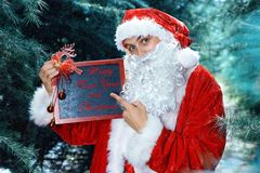 Santa Claus in a winter forest. Christmas and new year holiday. In his hands he holds a sign with congratulations royalty free stock photo