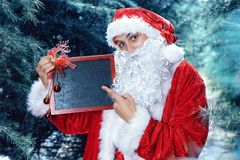 Santa Claus in a winter forest. Christmas and new year holiday. In his hands he holds a sign with congratulations stock image