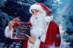 Santa Claus in a winter forest. Christmas and new year holiday. In his hands he holds a sign with congratulations royalty free stock images