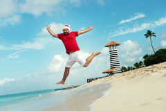 Santa Claus and wish a happy new year. Funny Grandfather Frost jumps on the sea. Tropical sandy beach - xmas travel vacation discounts and travel agencies Royalty Free Stock Photos