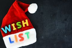 Santa Claus wish list concept with colorful text on Santa's red hat. Santa Claus wish list concept with colorful text on Santa's red hat on blackboard Stock Photography
