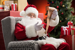 Santa Claus with wishlist in hands Stock Photo