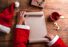 Santa Claus and wishlist. Santa Claus holding an empty wish list in his hands Royalty Free Stock Image