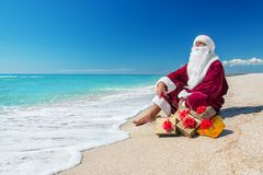 Free Santa Claus With Many Golden Gifts Relaxing At Beach Stock Photography - 34635562