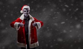 Santa Claus is a wizard with a skull on Christmas. Santa Claus is a wizard with a skull on Christmas against the background of the corpsepice Stock Image