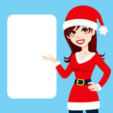 Santa Claus Woman. Beautiful burgundy haired woman in Santa Claus clothing showing a blank billboard sign Royalty Free Stock Image