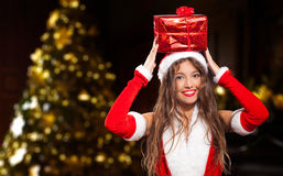 Santa Claus woman holding a gift on her head Royalty Free Stock Photography