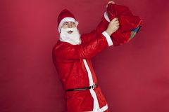 Santa Claus wonders that the bag is empty. On the red background Stock Photography