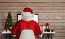 Santa Claus work on a computer in his office. Answer on letters and greeting cards via email