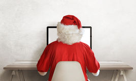Santa Claus work on computer. View from back. Free space beside from text. Empty work desk royalty free stock photo