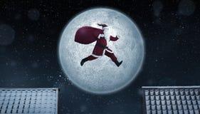 Santa Claus at work. Funny Santa Claus jumping between rooftops at night with bag full of gifts Stock Images