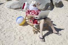Santa Claus working on beach chair working with laptop computer. Santa Claus in red swimming trunks ans Hawaiian shirt lounging on sandy beach with straw hat and royalty free stock images