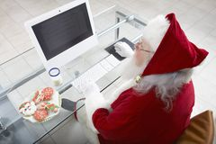 Santa Claus Working On Computer Royaltyfri Foto