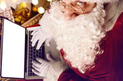 Santa Claus working on modern laptop Stock Photography