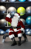 Santa Claus working out with dumb-bells Stock Images